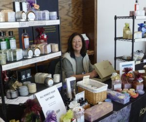 Miriam at a craft market surrounded by her handcrafted natural soaps.